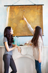 Two young women looking at old map
