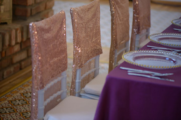 Sitting arrangement at a fine dining restaurant or event featuring transparent plates with golden details, glassware and silverware in the order of use with purple table cloth and sequins chair covers