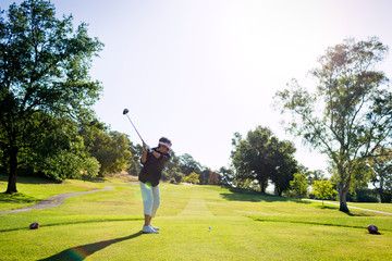 Portrait of female golfer doing swing on golf course