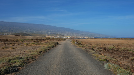 Empty road cutting through the arid volcanic lanscape of Tenerife island, road from Faro Punta de Abona towards the village Poris de Abona, concept for going the extra mile or clear work and lifestyle
