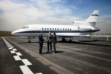 Two businessmen and businesswoman standing on runway nearby private jet