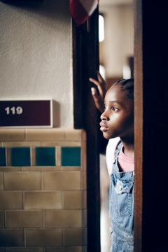 Student looking through open door