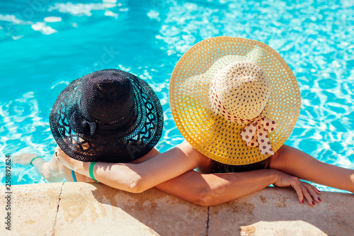 Mother and her adult daughter relaxing in hotel swimming pool. People enjoying vacation. Mother's day