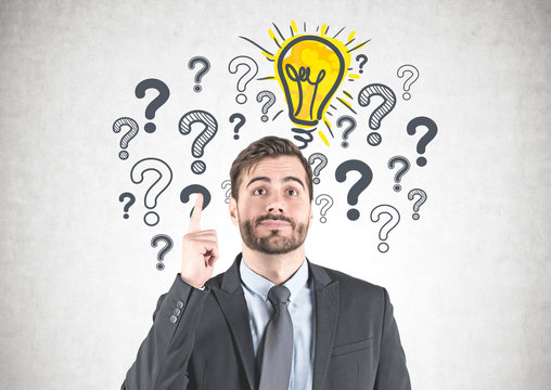 Businessman with idea, question marks and bulb