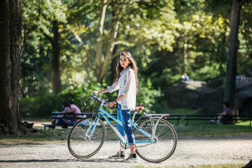 Portrait of young woman with bicycle
