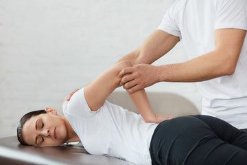 Female patient doing physical exercises with physiotherapist. Male therapist treating injured shoulder of young athlete. Post traumatic rehabilitation, sport physical therapy, recovery concept.