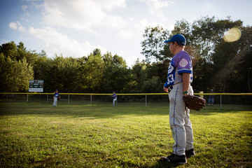 Young baseball player (8-9) in playing field