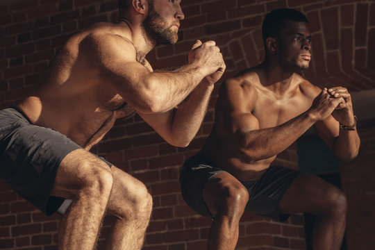 Two multi ethnic male sportsmen are jumping on plyo box, close up. African fitness instructor with his caucasian trainee doing box jump workout at cross fit gym