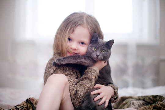 Young girl (4-5) holding cat