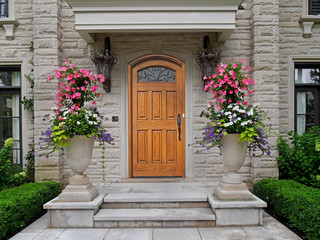 elegant wooden front door of stone house with large flower pots