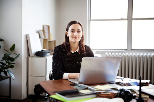 Portrait of young woman using laptop in office