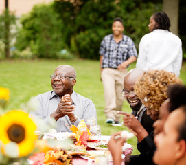 Family members with teenagers laughing at family reunion outdoors