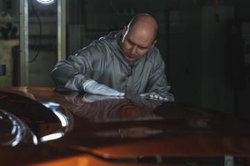 Fototapeta An employee of the car body painting shop checks the quality