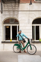 Man in front of building with bicycle,