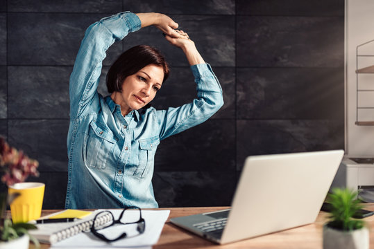 Business woman stretching arms in the office
