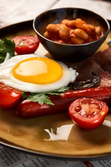Full English breakfast with bacon, sausage, fried egg, baked beans