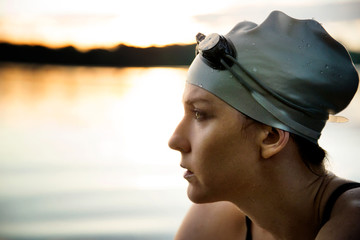 Close up of woman in swimming cap at dusk