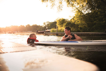 Man with son standing in lake next to paddleboards and laughing