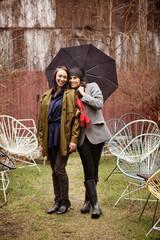 Two women sharing umbrella
