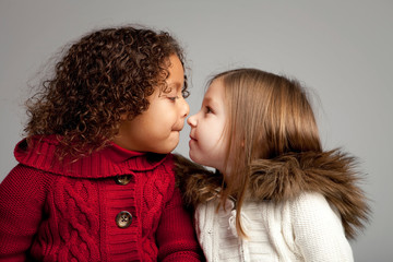 Studio shot of two girls (4-5, 6-7) looking at each other