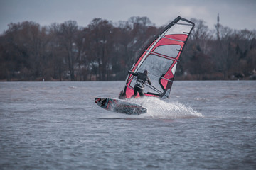 Windsurfer on the Rhine jumps out of the water. Water splashes. Cold colours and a bit evening sun.