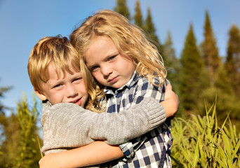 Boy and girl (4-5, 6-7) embracing in grass