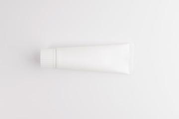 Blank white tube of toothpaste, cream or gel standing on white background. Branding mockup