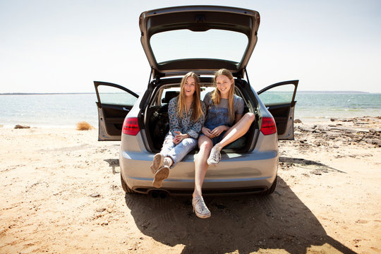 Young women sitting in car trunk on beach