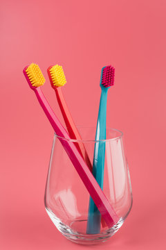 Cup with toothbrushes on table against color background. Dental care