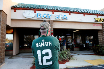 New York Jets fan Kevin Brown of Jupiter takes a picture in front of Orchids of Asia Day Spa & Massage in Jupiter