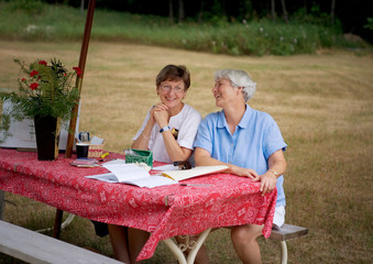 Women talking at table in backyard
