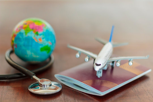 Stethoscope , passport document, airplane and globe. Healthcare and travel insurance concept