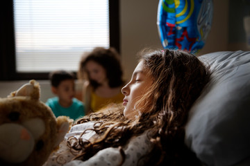 Girl (8-9) sleeping in hospital ward and mother on background