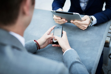 Two businessmen sitting at table using smart phone and digital tablet
