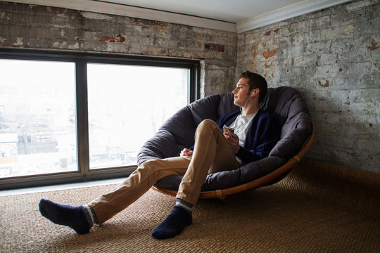 Young man listening to MP3s in loft apartment