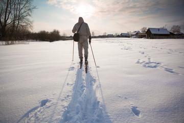 Man cross country skiing through farm area