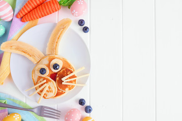 Easter Bunny breakfast pancakes on a white plate. Side border against a white wood background with copy space.