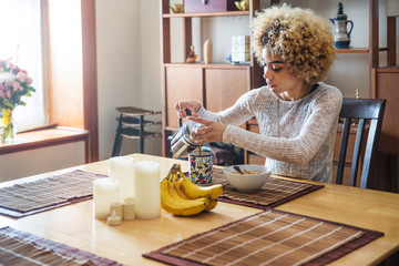 Young woman having breakfast in kitchen,