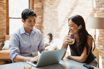 Mid adult couple in modern house interior, alcoholic drink, laptop on table