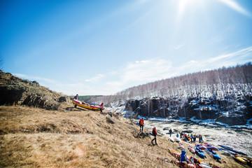 People preparing kayaks for river trip