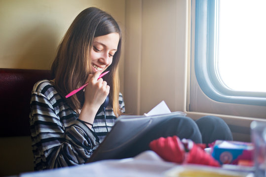 Young smiling woman writing in notebook