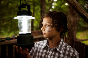 Boy (8-9) with face painted, holding lamp in wooden built structure forest in background