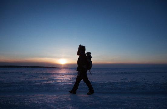 Woman walking on frozen lake at sunset