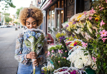 Young woman buying flowers in street,