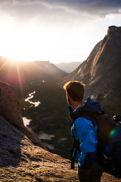 Young man looking at mountains at sunset