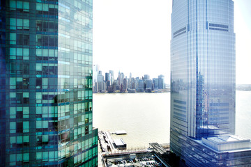 View between two skyscrapers of city skyline on river