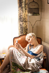 Woman sitting in armchair using cell phone
