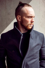 Young man in black coat looking away