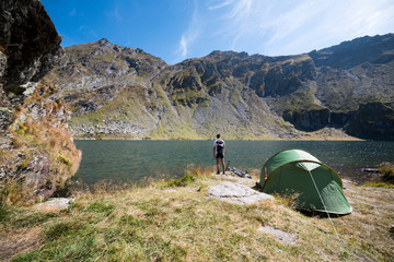 Mountain biker camping on lakeshore