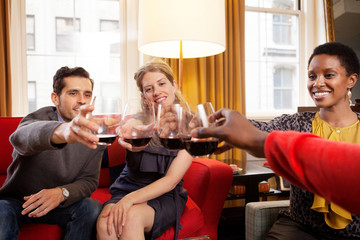 Group of friends raising toast at home